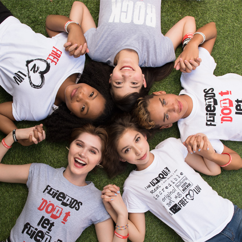 girls and boys laying on the grass and holding hands. Wearing Free2Luv tshirt.